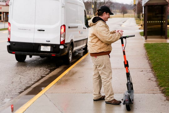 A Spin Scooters employee moves a scooter from the sideway on Purdue University's campus to a van, Wednesday, March 18, 2020 in West Lafayette