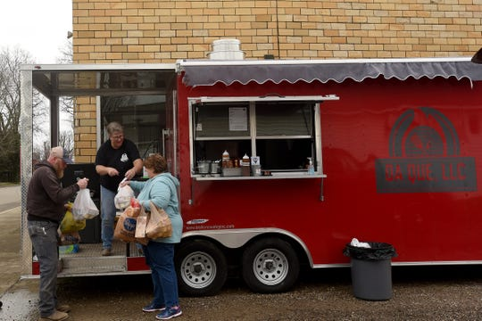 Customer Chad Reihing helps Da Que co-owner Amy Vannoy load up Amanda-Clearcreek cafeteria supervisor Kimberly Dum with donated food for the school on Thursday, March 19, 2020. The local food truck asked people to drop off any food they had to donate for local kids while also offering a free lunch to kids in the community from their truck.