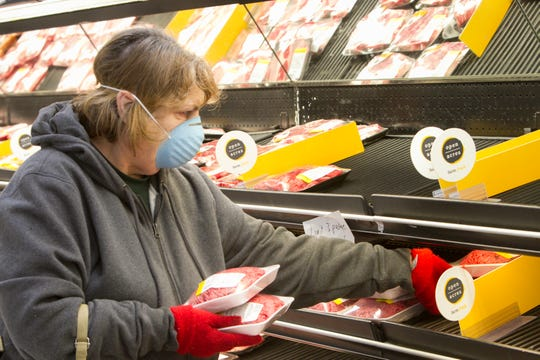 Pat VanPatten wears a mask out of consideration for others as she shops at the Howell VG's Grocery store Thursday, March 19, 2020. VanPatten says she fortunately had the mask from the H1N1 flu outbreak since none can be found now.