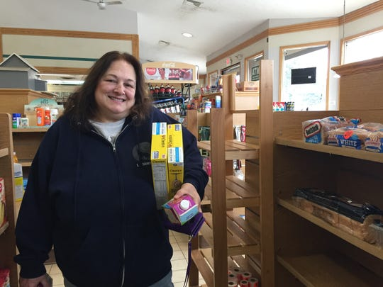 Diane Hoskins grabs Cheerios and half-and-half at small grocer and liquor store Vic & Bob's in Genoa Township, Thursday, March 19, 2020. Hoskins said the items weren't available at Kroger when she and her husband picked up a grocery order there.