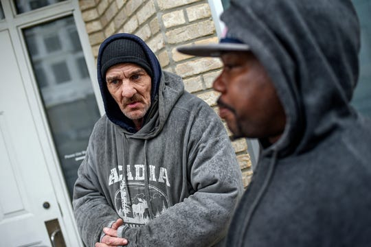 Mark Korkoskie, left, and Larry Wilder wait in line before dinner outside the City Rescue Mission on Wednesday, March 18, 2020, in Lansing.