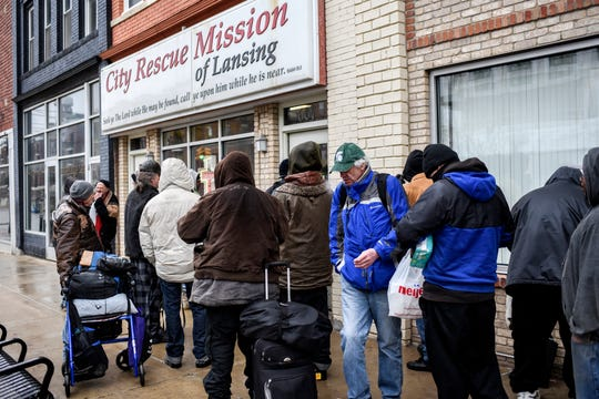 People file into the City Rescue Mission of Lansing on Wednesday, March 18, 2020, in Lansing.