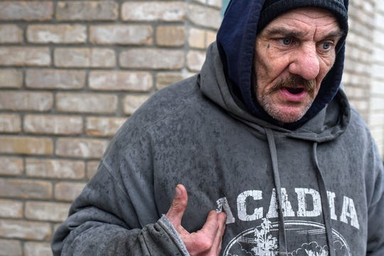 Mark Korkoskie talks about the coronavirus changes at the City Rescue Mission of Lansing as he waits outside the building before dinner time on Wednesday, March 18, 2020, in Lansing. Korkoskie has been homeless for about six months.