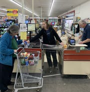 "At center, Julie Huguelet, an assistant manager at Darrell's Market & Hardware, scans groceries for a customer on Wednesday, March 18, 2020. Tuesday an anonymous customer handed her an envelope with $1,000 cash inside and asked that it be equally divided among the store's staff. Amid the ""crazy busy"" week of keeping up with constant sales and stocking of products the gift is a reminder, she said. ""Not everybody out there is hoarding toilet paper. There are nice people out there."""
