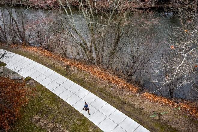 A man runs along the Red Cedar River behind the Computer Center on Thursday, March 19 2020, on the Michigan State University campus in East Lansing.