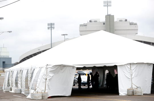 Preliminary construction of a drive-thru coronavirus testing site is erected as first responders practice a dry run outside the Liberty Bowl Memorial Stadium on Thursday, March 19, 2020.