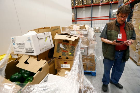 Charles Abraham, a warehouse receiving clerk at the Mid-South Food Bank, looks over the seven pallets with over 4000 pounds of food supplies donated by Horseshoe Casino after their operations were shut down due to concerns of the spread of coronavirus on Thursday, March 19, 2020.