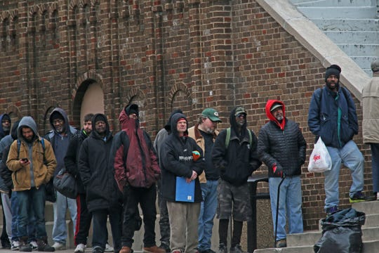 People line up for the evening meal at St. Benedict the Moor Parish at 924 W. State St., Milwaukee, on Monday. The homeless population is a group vulnerable to the coronavirus pandemic.
