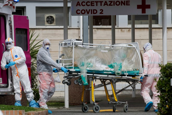 Patients with COVID-19 are often isolated from family to prevent spreading the virus. For the sickest patients in Wisconsin, that has meant saying goodbye over a phone or not at all. In this photo, a patient is carried on a stretcher into a hospital in Rome.