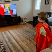 "Three-year-old Weston Rodriguez watches a live stream of the ""Miss Maria Rhyme Time"" from his living room."