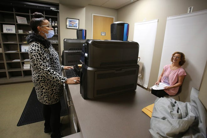 Service representative Lisa Norwood, left, wears a mask as she takes a driver's license photo of Jamie Easton of North Little Rock at the Central Revenue Office in Little Rock on Wednesday.