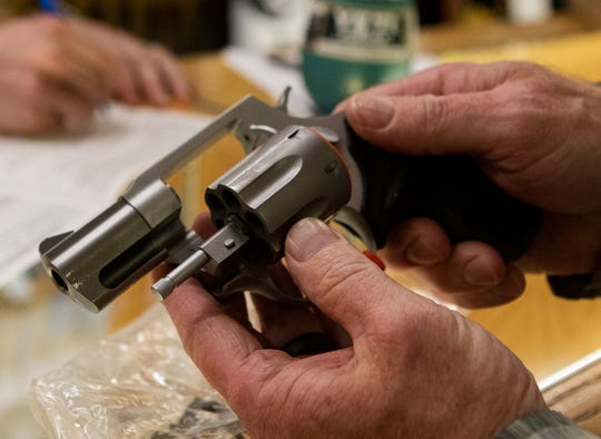 A customer at T.P. Outdoors in Monroe, La. inspects a handgun on March 19.
