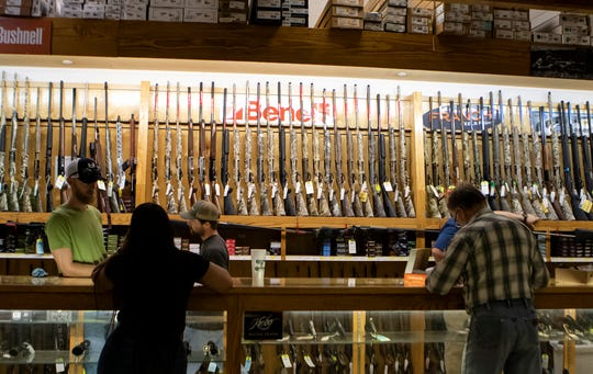 Customers at T.P. Outdoors in Monroe, La. view weapons at the counter on March 19.