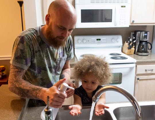 Lanier teacher Ryan Dalton and his daughter, Teige, 2, wash their hands at their home in Montgomery, Ala., on Thursday, March 19 2020.