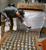 Distillery worker Tyler Crowell packs bottles of hand sanitizer at Corsair Distillery Thursday, March 19, 2020 in Nashville, Tenn. Corsair Distillery has halted production of their spirits and converted their operation to produce hand sanitizer to donate to those in need during the Coronavirus outbreak.