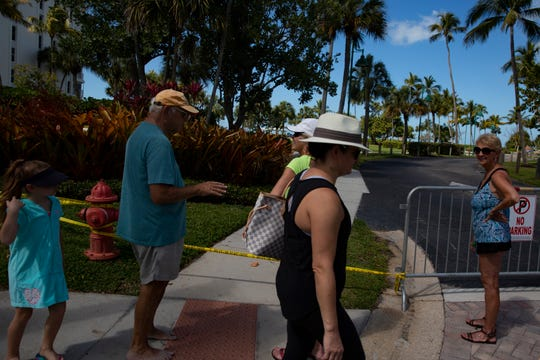 Community members walk past the closed entrance to Lowdermilk Park in Naples on Thursday, March 19, 2020.