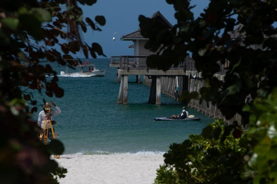 A city worker, left, and kayak and a pair of kayak anglers work along  the Naples Pier on Thursday, March 19, 2020.