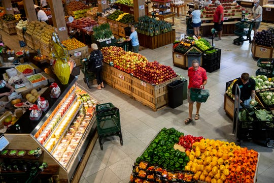 Shoppers look through the produce section at Oakes Farms Seed to Table Market in Naples on Thursday, March 19, 2020.