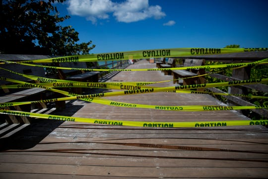 Yellow caution tape is used to close off the Naples Pier onThursday, March 19, 2020.