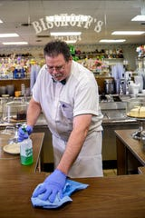 Steven Mather of Bischoff's ice cream shop in Teaneck, NJ wipes down the counter on Thursday March 19, 2020. Bischoff's and other local stores are trying to adapt to new complications due to the Coronavirus.