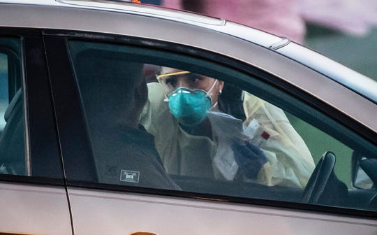 Medical personnel check a person at a mobile site for coronavirus testing across the street from Lovelace Hospital on Friday afternoon, March 13, 2020, in Albuquerque.