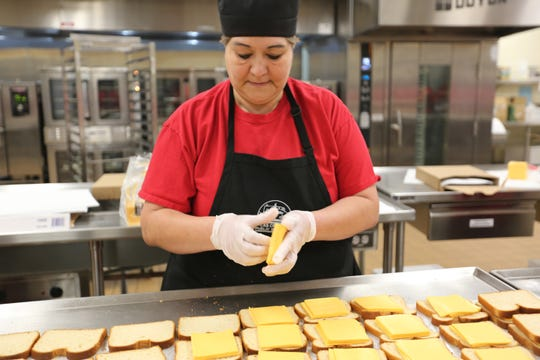Las Cruces Public Schools worker Veronica Muniz helps prepare grilled cheese sandwiches at Las Cruces High School on Thursday March 19, 2020.