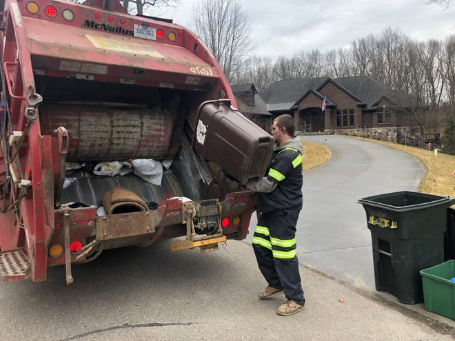 A GFL employee picks up trash in Milford in this March 2020 photo. The company has come under fire from residents frustrated with delays in garbage pickups.