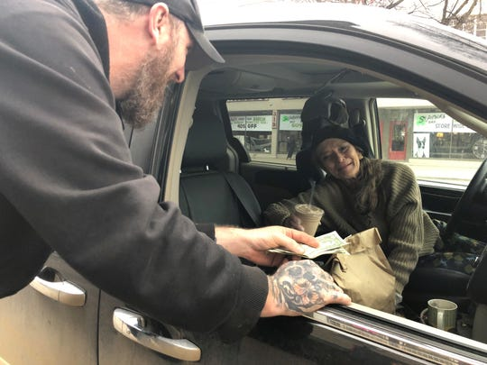 Brian Belwood, owner of the Burger Joint in Milford, delivers a curbside carryout order to Joan Giannola on March 18, 2020.