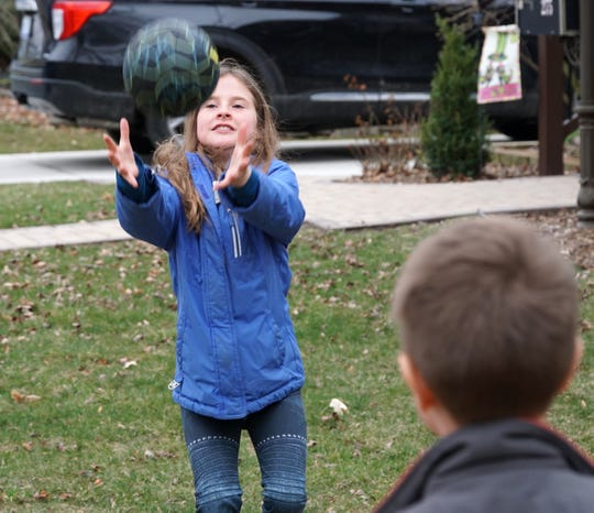 Keira Mueller, 9, plays catch with one of her Adams Street neighbors in Plymouth on March 19, 2020.