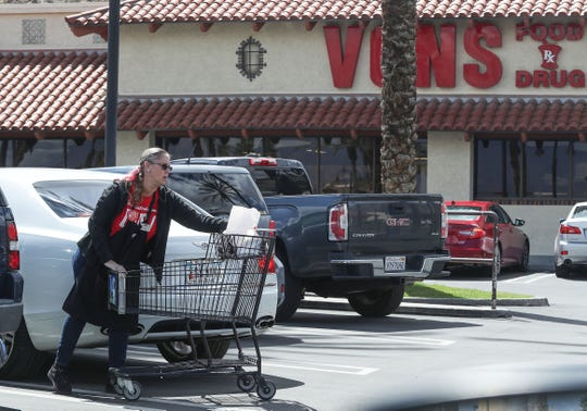 A Vons grocery employee helps a customer get her groceries loaded in her car in La Quinta, March 19, 2020.