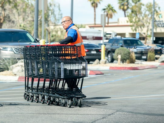 A grocery store employee at Stater Brothers rounds up carts in their parking lot in La Quinta, March 19, 2020.