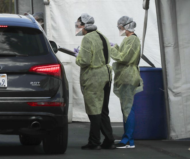 Two health care workers screen a possible coronavirus patient at a drive-thru testing facility in Indian Wells, Calif., March 19, 2020.