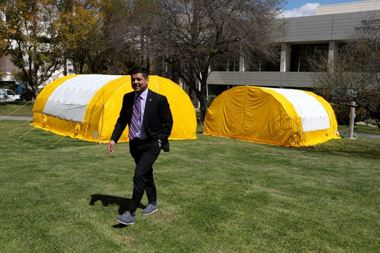 Rep. Raul Ruiz walks away from the empty triage yellow tents set up at Desert Regional Medical Center after taking a look inside prior to a press conference at the hospital in Palm Springs, Calif., on Thursday, March 19, 2020.