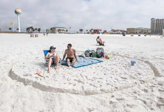 "Megan and Tim Deselms, of Gulf Breeze, sit within their ""circle moat of safety"" at Casino Beach in Pensacola on Thursday, March 19, 2020."