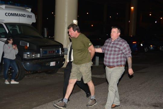 Pensacola Police Department Sgt. Danny Harnett (right) and Captain Chuck Mallett walk Daniel Leonard Well to booking Wednesday night.