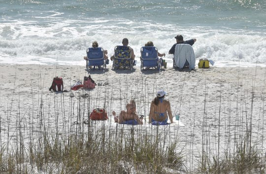 Beachgoers relax at Pensacola Beach on Thursday, March 19, 2020. District 4 county commissioner Robert Bender announced that Pensacola Beach will remain open, but hotel capacity will be reduced to 50%.