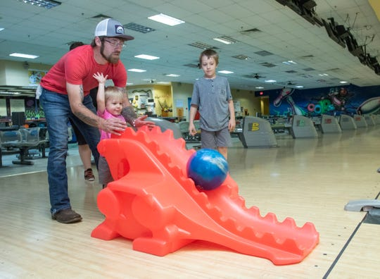 Ace Blocker, 7, looks on as Sebrin Blocker helps Zayden Kia, 2, bowl at Oops Alley in Pace on Thursday, March 19, 2020.