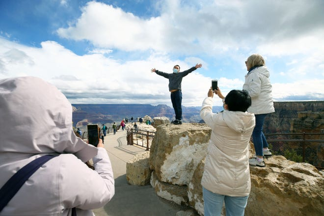 A Taiwanese tourist has his picture taking while wearing a N-95 mask at Mather Point at Grand Canyon National Park in Arizona on Mar. 18, 2020.