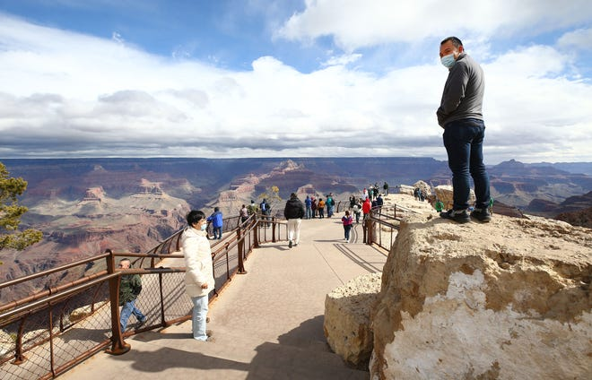 Two Taiwanese tourists wear N-95 masks while taking in the view at Mather Point at Grand Canyon National Park in Arizona.