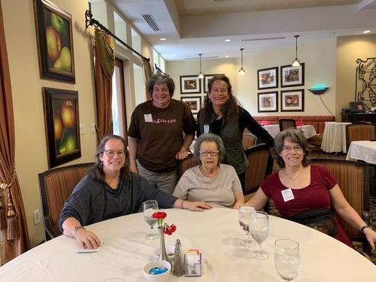 Amy Clague, center, is surrounded by her family and assisted living facility employees. Since her family can't visit, Clague has spent her time walking for exercise, reading The New York Times and calling her daughters.