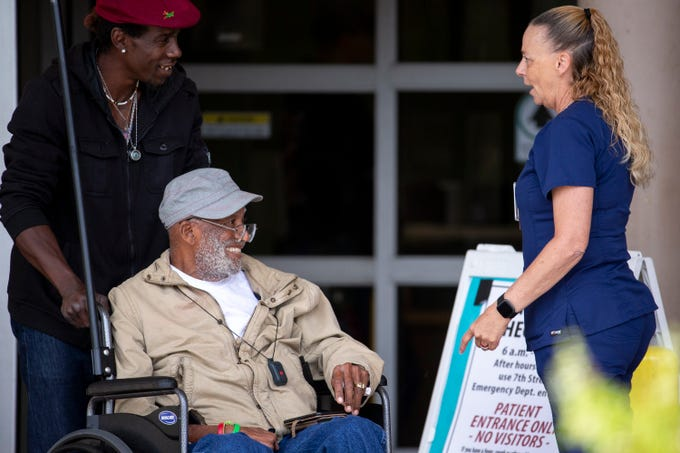 A Phoenix VA employee talks to people at a hand-washing tent outside the main entrance on March 19, 2020, in Phoenix.