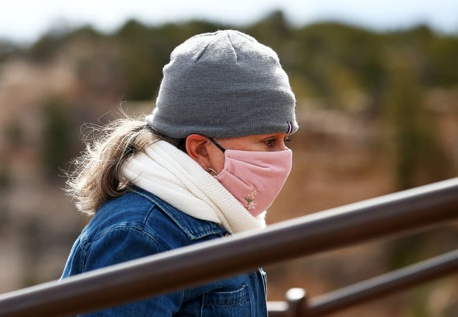 A tourist wears an N-95 mask at Mather Point at Grand Canyon National Park in Arizona on March 18, 2020.