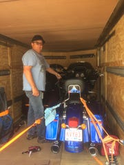 Terri Bozok's husband, Donnie Bozok, packs motorcycles in their trailer as they prepare to leave Arizona early.