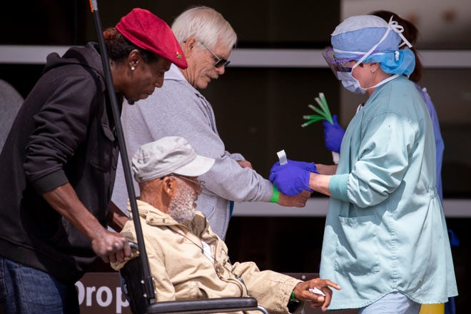 A Phoenix VA employee puts a wristband on a man at a hand-washing tent outside the main entrance on March 19, 2020, in Phoenix.