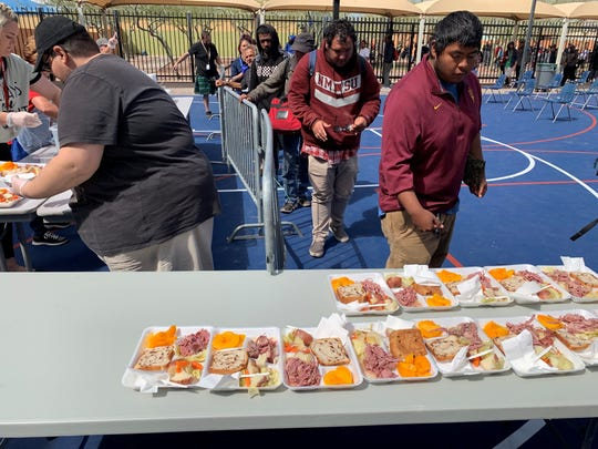 """St. Vincent de Paul has had to restructure its """"social embracing"""" model to continue serving 4,000 meals a day to the homeless and less fortunate. Instead of communal tables in the dining room, guests are served on individually spaced chairs outside."""