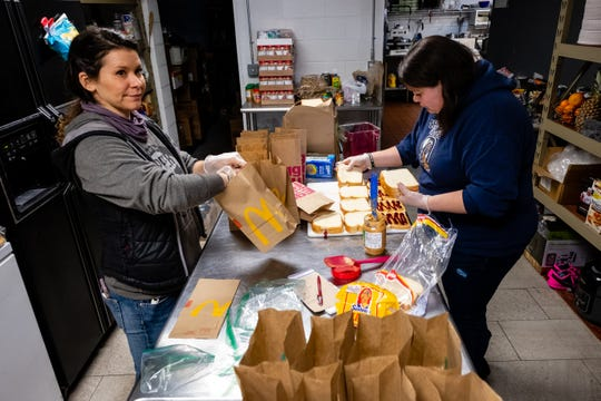 Volunteers Stacie Catron, left, and Katrina Hill make peanut butter and jelly sandwiches in the kitchen of Port Huron Lanes Thursday, March 19, 2020.