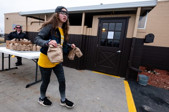 Fort Gratiot Middle School seventh-grader Emily Tonsor, 12, carries bags of food to a car Thursday, March 19, 2020, outside Port Huron Lanes. Volunteers are hosting food drives in the parking lot of the bowling alley 11 a.m.-1 p.m. Monday thru Friday and are giving out up to 250 meals.