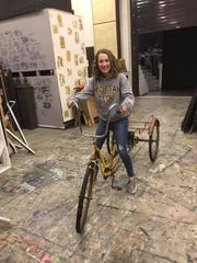 "Student director Averi Reno rides a bike during rehearsals for the Port Huron Northern High School production of ""Big Fish."""