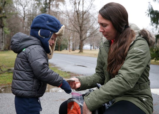 Jen Raymo gives a snack to her son Ryan, while taking a hike at Vanderbilt Mansion National Historic Site in Hyde Park on March 19, 2020.