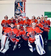The York Devils 14U AA taking a photo with their DVHL championship banner.